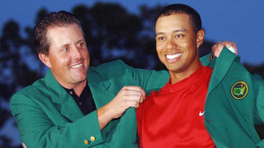 Tiger Woods (R) is awarded his green jacket by 2004 champion Phil Mickelson at the 2005 Masters Golf Championship.