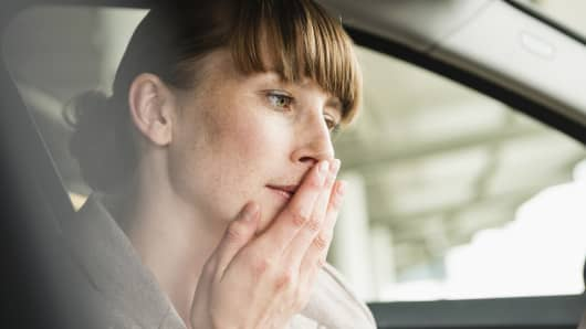 Woman in car with hand over mouth