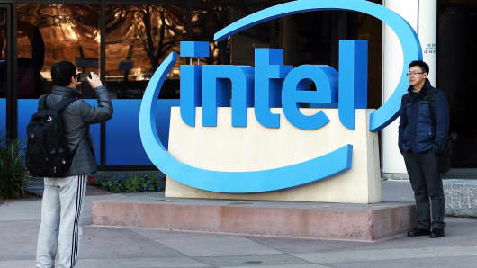 Visitors take pictures next to the Intel logo outside of company headquarters in Santa Clara, California.