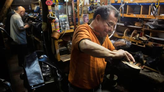 An employee repairs shoes at Jim's Shoe Repair in New York, March 11, 2015.
