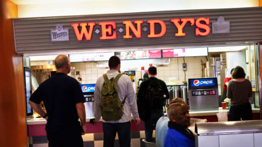 People wait on line at a Wendy's location
