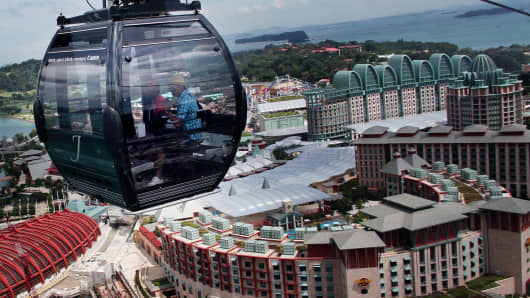 Tourists take in a cable car take in the sights at Sentosa Island, Singapore