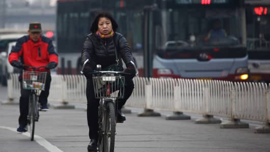 Commuters ride bicycles near buses in the central business district of Beijing, China.