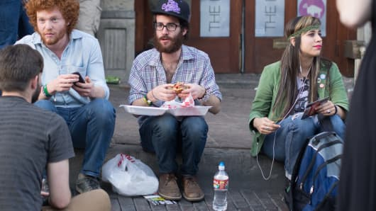 Young, stylish hipsters sit on the curb while eating street food on 6th Street in Austin, Texas.