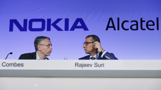 Alcatel-Lucent's CEO Michel Combes (L) and Nokia's Chief Executive Rajeev Suri