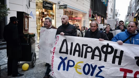 Protesters march on April 9, 2015 with a banner, reading 'Write off the debt now,' during a small protest in Athens.
