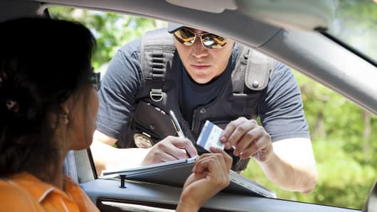 Woman receiving speeding ticket from police officer