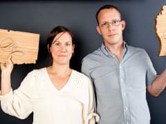 Amy Stringer-Mowat and Bill Mowat holding state-shaped cutting boards