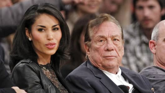 In this Dec. 19, 2010 photo, Los Angeles Clippers owner Donald Sterling, right, sits with V. Stiviano as they watch the Clippers play the Los Angeles Lakers during an NBA preseason basketball game in Los Angeles.