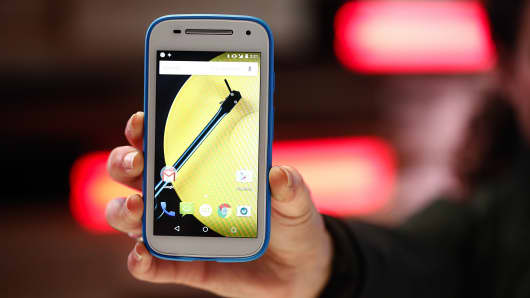 An employee demonstrates a Motorola Moto E android smartphone in the Lenovo Group Ltd. pavilion at the Mobile World Congress in Barcelona, Spain.