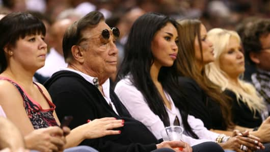 Former team owner Donald Sterling of the Los Angeles Clippers and V. Stiviano watch the San Antonio Spurs play