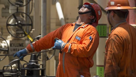 A worker looks up while changing a drill pipe on the Laurus oil drilling rig operated by Petroleos Mexicans (Pemex) in the Ku-Maloob-Zaap oilfield at Campeche Bay off the coast of Ciudad del Carmen, Mexico.