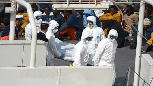 Rescued migrants watch as the body of person who died after a fishing boat carrying migrants capsized off the Libyan coast, is brought ashore along with 23 others retrieved by the Italian Coast Guard vessel Bruno Gregoretti at Boiler Wharf, Senglea in Malta on April 20, 2015.