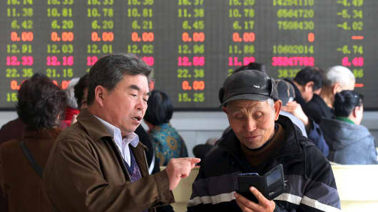 Investors talk in front of an electronic board showing stock informations at a brokerage house in Kaifeng, Henan Province.