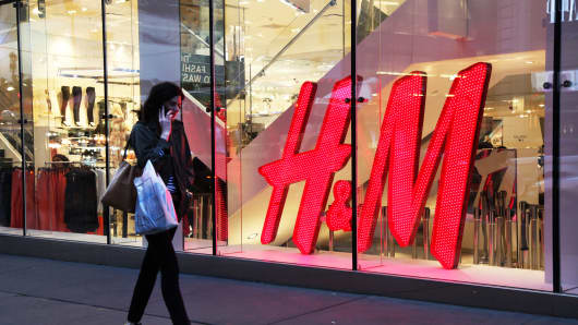 A woman walks past an H&M store in New York