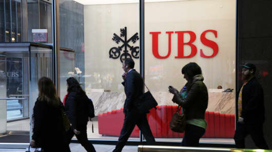 People walk past UBS offices in New York