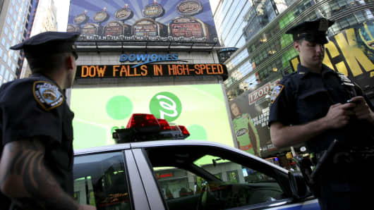 A New York City police officer, left, looks at a news ticker in Times Square displaying news about the Dow Jones Industrial Average in New York, U.S., on Thursday, May 6, 2010.