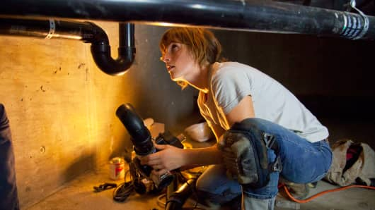 A woman installs a diverter valve for a greywater system at a new home in Los Angeles.