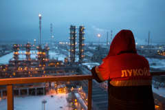 An employee looks out over the illuminated petroleum cracking complex at the Lukoil-Nizhegorodnefteorgsintez oil refinery, operated by OAO Lukoil, in Nizhny Novgorod, Russia.