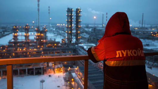An employee looks out over the illuminated petroleum cracking complex at an oil refinery operated by OAO Lukoil, in Nizhny Novgorod, Russia.