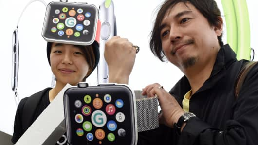 Holding the packaging for the new Apple Watch, Makoto Saito (L) and her friend Kazumi Oda (R) pose after getting a new watch at a telecom shop in Tokyo on April 24, 2015.