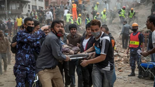 Emergency rescue workers carry a victim on a stretcher after Dharara tower collapsed on April 25, 2015 in Kathmandu, Nepal.