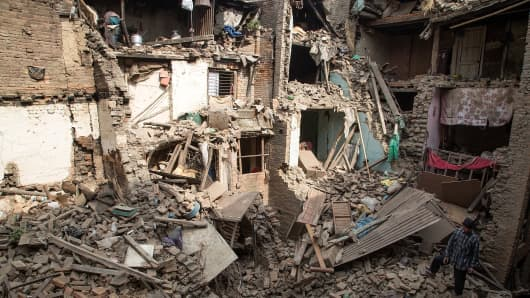 A man stands on top of debris from collapsed buildings on April 26, 2015 in Bhaktapur, Nepal.