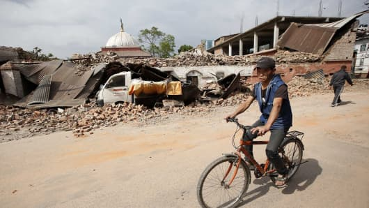 A Nepali on a bicycle pass by a truck buried under debris of destroyed buildings in Katmandu, Nepal on April 26, 2015