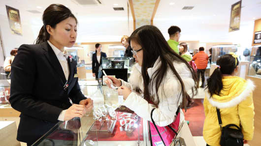 A Chinese tourist, right, inspects a wrist watch at a Laox Co. store in the Ginza district of Tokyo, Japan.