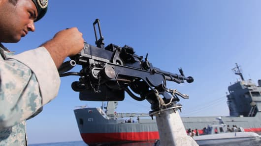 File photo of an Iranian Army soldier stands guard on a military speed boat.