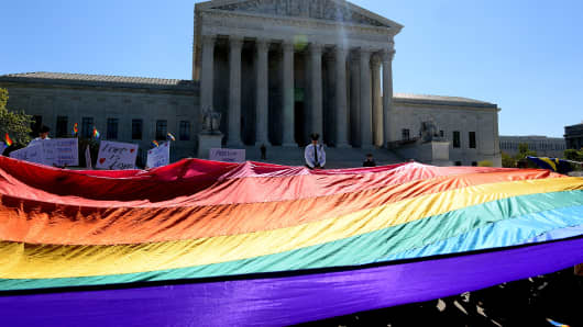 Protesters hold pro-gay rights flags outside the US Supreme Court on April 28, 2015 in Washington, DC. The Supreme Court meets to hear arguments whether same-sex couples have a constitutional right to wed in the United States, with a final decision expected in June.