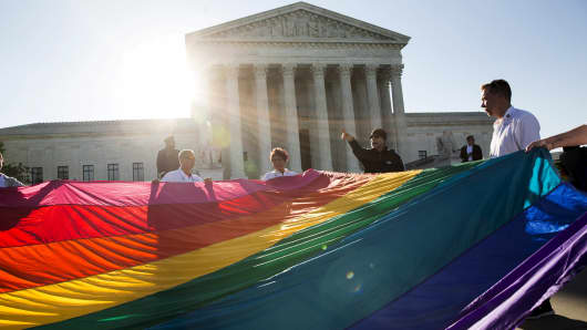 Gay marriage supporters hold a gay rights flag in front of the Supreme Court in Washington April 28, 2015.