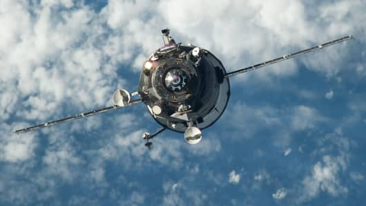 An unpiloted Progress resupply vehicle is shown approaching the International Space Station.