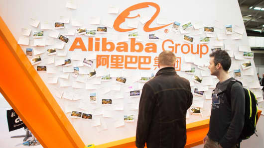 Visitors stand in front of the Alibaba Group stand at the 2015 CeBIT technology trade fair on March 20, 2015 in Hanover, Germany.