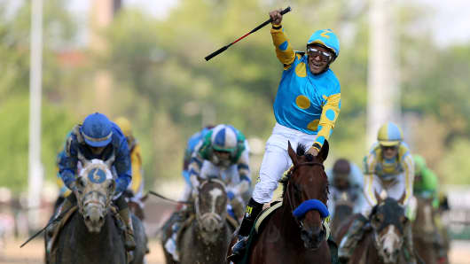Jockey Victor Espinoza celebrates as he guides American Pharoah #18 after crossing the finish line to win the 141st running of the Kentucky Derby at Churchill Downs on May 2, 2015 in Louisville, Kentucky.