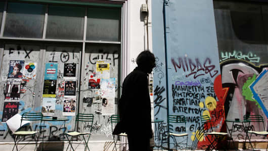 :Graffiti covers the shopping windows of closed shops, as a pedestrian walks past, in Athens, Greece.