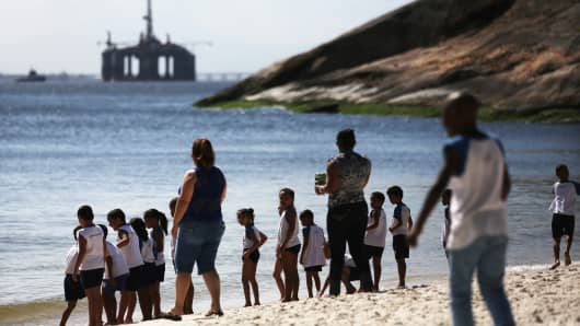 Schoolchildren play on a beach in front of an oil platform in Brazil.