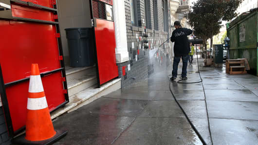 A worker uses a power washer to clean the sidewalk in front of a building on May 6, 2015, in San Francisco. The California State Water Resources Control Board approved California Gov. Jerry Brown's proposed emergency drought regulations that will slash water use in urban areas by an average of 25 percent.