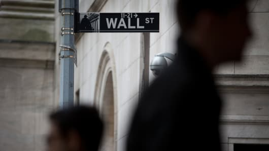 Pedestrians pass in front of a Wall Street sign in New York.