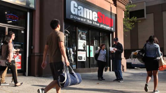 Pedestrians pass in front of a GameStop store in New York