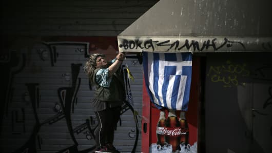 A trader hangs a Greek national flag from the roof of a kiosk store in Thessaloniki, Greece.