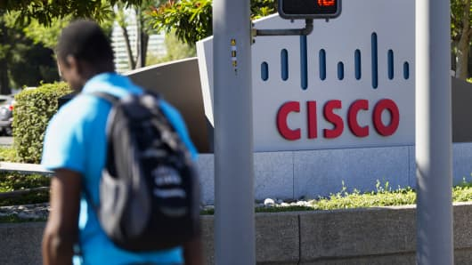 A pedestrian walks past Cisco Systems signage at the company's headquarters in San Jose, Calif.