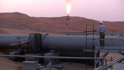 A worker stands at a pipeline, watching a flare stack at the Saudi Aramco oil field complex facilities at Shaybah in the Rub' al Khali ('empty quarter') desert in Shaybah, Saudi Arabia.