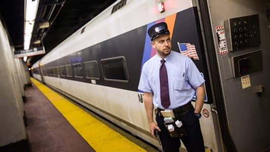 NJ Transit conductor John Nagle waits for passengers to board the NJ Transit train from New York's Penn Station to Trenton, N.J., May 13, 2015, in New York.