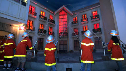 Children spray water at a simulated fire site as they play the roles of firefighters at KidZania Tokyo.