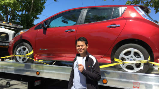 Dan Delima of Millbrae, California, holds a check from Beepi after selling his Nissan LEAF (on the flatbed truck behind him) to the used car website.