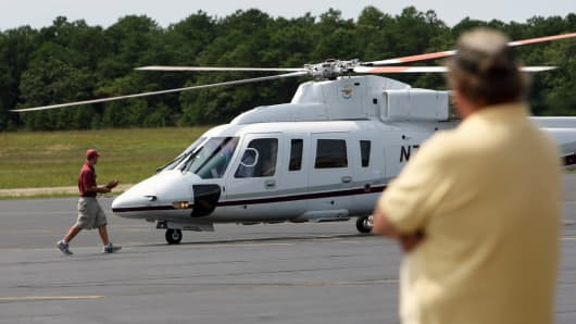 A man watches a helicopter at the East Hampton Airport in East Hampton, New York, in August of 2007.