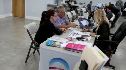 A couple sit with an insurance advisor with UniVista Insurance company, as they sign up for the Affordable Care Act in Miami.