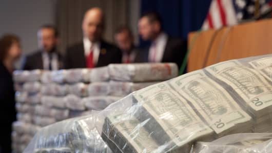 Sacks of money, right, worth $2 million, and 154 pounds of heroin, left, worth at least $50 million, are displayed at a Drug Enforcement Administration news conference, Tuesday, May 19, 2015 in New York.