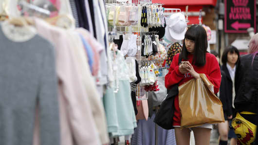A woman uses her mobile device outside a clothing store in the Harajuku district of Tokyo, Japan.